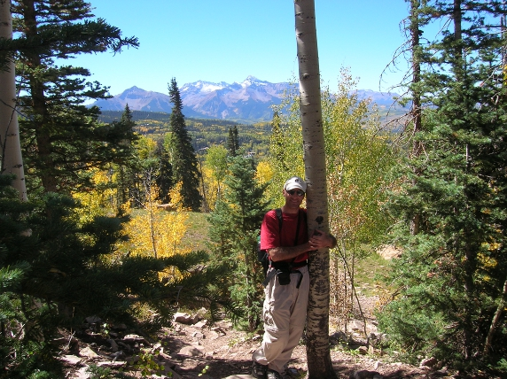 Marc hugging aspen tree on trail in Telluride